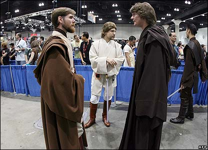 Two fans in Jedi costume prepare to use the Force
