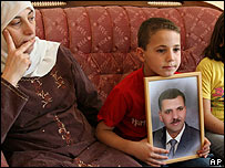 La esposa del ministro de Educación, Nasser Shaer, junto a su hijo, muestran su foto