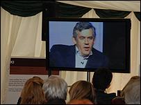 Festival goers watch Gordon Brown on a screen