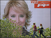 Gente camina cerca de un enorme afiche de Esperanza Aguirre, la candidata del opositor PP al gobierno de Madrid