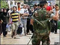 Refugees leaving the Nahr al-Bared camp approach a military checkpoint on 26 May 2007