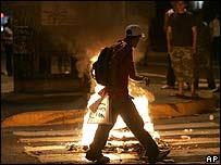 Un manifestante camina entre llantas quemándose