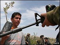 Palestinian youth holding olive sapling faces Israeli soldier in West Bank