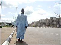 Man walks down deserted street in Abuja