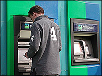 Customer taking money from a Lloyds TSB cash point