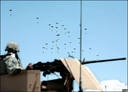 A US soldier looks on as a C17 plane drops supplies in Ghazni province, Afghanistan, south-west of the capital, Kabul.