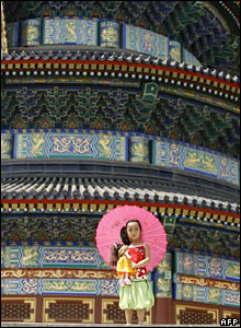 A young girl clutches her doll whilst visiting the Temple of Heaven in Beijing.