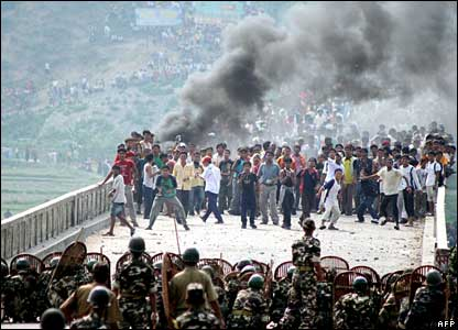 Bhutanese refugees hurl stones at Indian security forces trying to prevent them from crossing the border at India Mechi River Bridge