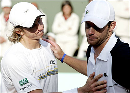 Andy Roddick (L) is consoled by Igor Andreev