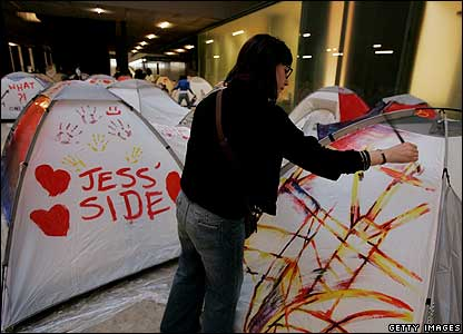 A girl paints a tent, which is part of an exhibition at the Tate Modern Turbine Hall in London, UK