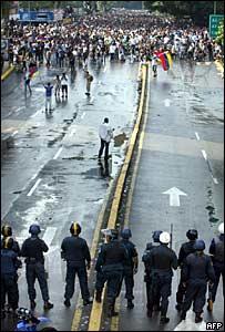 Manifestantes en contra del gobierno en fila frente a la policía antimotines en Caracas