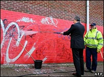 Tony Blair cleaning graffiti from a wall