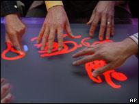 Varias manos dibujan sobre la pantalla de Surface