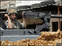 A Lebanese soldier sits on top of his armoured vehicle at the outskirts of the besieged refugee camp of Nahr al-Bared in north Lebanon, 30 May 2007