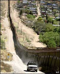A US border patrol agent by the border fence in Nogales, Arizona