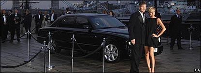 David and Victoria Beckham stand next to a car