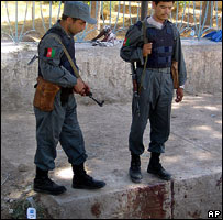 Afghan police officers stand near blood stains after 28 May protest