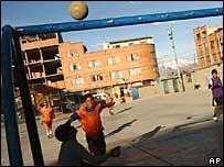 Estudiiantes juegan futbol en un patio escolar en Bolivia
