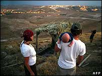 Jewish settlers look towards the lights of the West Bank settlement of Nofei Prat, east of Jerusalem, 29 May 2007
