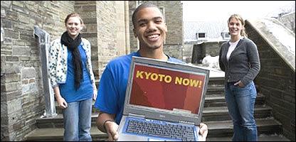 """Carlos Rymer y otras dos estudiantes con una computadora en la que se lee """"Kioto Ahora"""""""