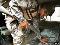 An Iraqi soldier searching a vehicle
