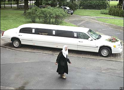 A woman walks past a wedding limousine outside an orthodox cathedral in Riga, Latvia, Friday, June 1, 2007.