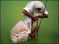 رجل دين مندائي يقوم بتعميد  مندائي