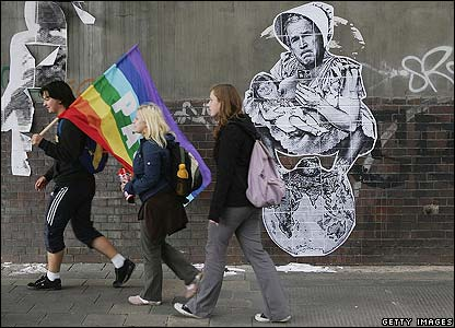 Protesters walk past a mural showing US President George W Bush and German Chancellor Angela Merkel