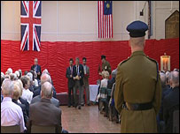 A veteran collects his medal at the ceremony in Rusholme