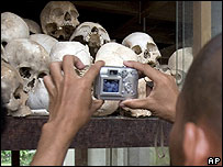 Cambodian monk takes a picture of human skulls at Choeung Ek killing field in Phnom Penh, Cambodia - 31/05/07