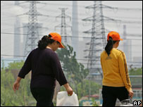Women walk past a row of electric pylons in front of a coal-fired power plant on the outskirts of Beijing.