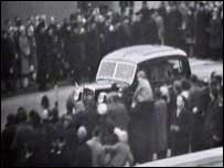 Crowds watch as the hearse carrying Sir Winston Churchill passes by
