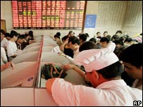 Investors check stock prices at a securities company in Shanghai