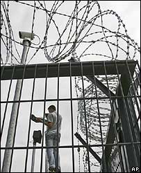 A man fixes a CCTV camera inside a security fence