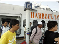 Passengers disembark from a ferry along the harbour front in Singapore after arriving from Indonesia's nearby Batam island, 25 April 2007
