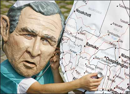 A protester wearing a Bush mask holds a stethoscope to a giant map of Africa  (06-06-07)