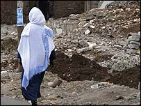 Woman walks past demolished house