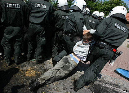 Riot police remove an anti-G8 activist from a blocked road near Bollhagen