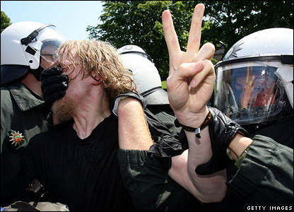 Riot police arrest an activist as they block a street