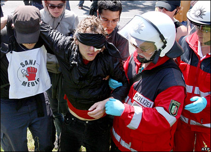 An injured anti-G8 activist is helped away by police from a blocked road