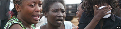 Unidentified people cry at the main mortuary in Nairobi hours after Kenyan police killed 20 suspected members of a religious sect called Mungiki (It is unknown if the women pictures are relatives of a