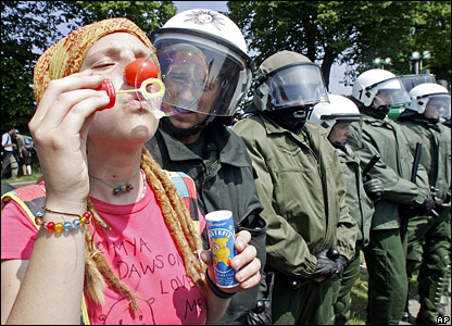 An anti-G8 protestor blows bubbles in front of a line of riot police