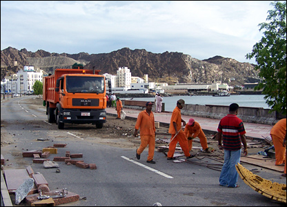 Workmen clear up some of the debris created by Cyclone Gonu