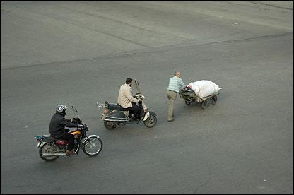 Motorcyclists manoeuvre around a cart on the city's Saadi Street.