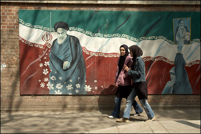 Two women walk past a poster of Iran's former leader Ayatollah Khomeini.