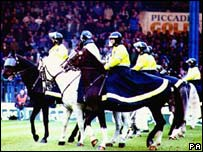 Police with horses on football pitch
