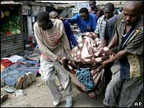 Men forced to carry a body in Mathare slum past people lying on the ground