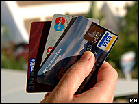 A person holding a selection of credit cards