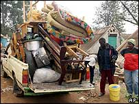 People packing their belongings onto a truck