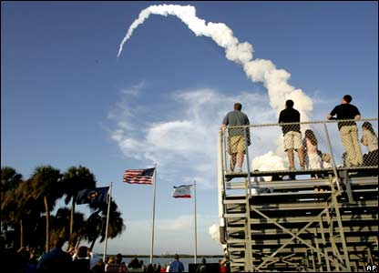 Spectators watch as space shuttle Atlantis lifts off from the Kennedy Space Center.